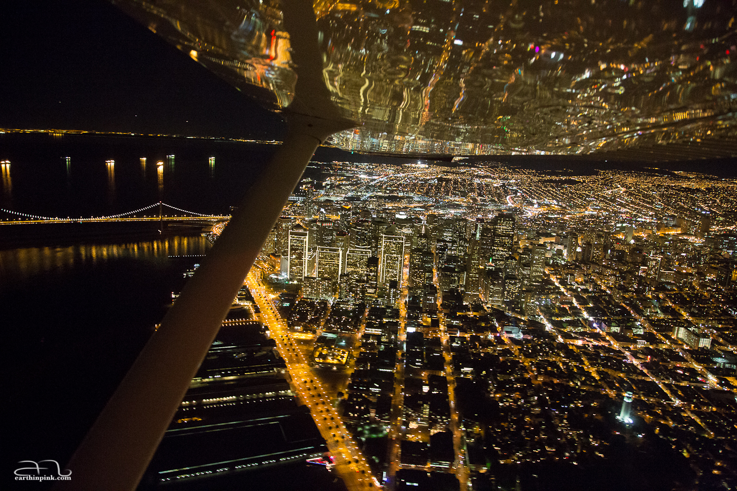 Night flying over San Francisco in a small Cessna plane, whose wing is reflecting the city lights below.