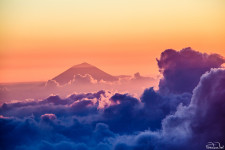 Sunset viewed from Gunung Rinjani in Indonesia, with Bali's Gunung Agung volcano peeking through the clouds.