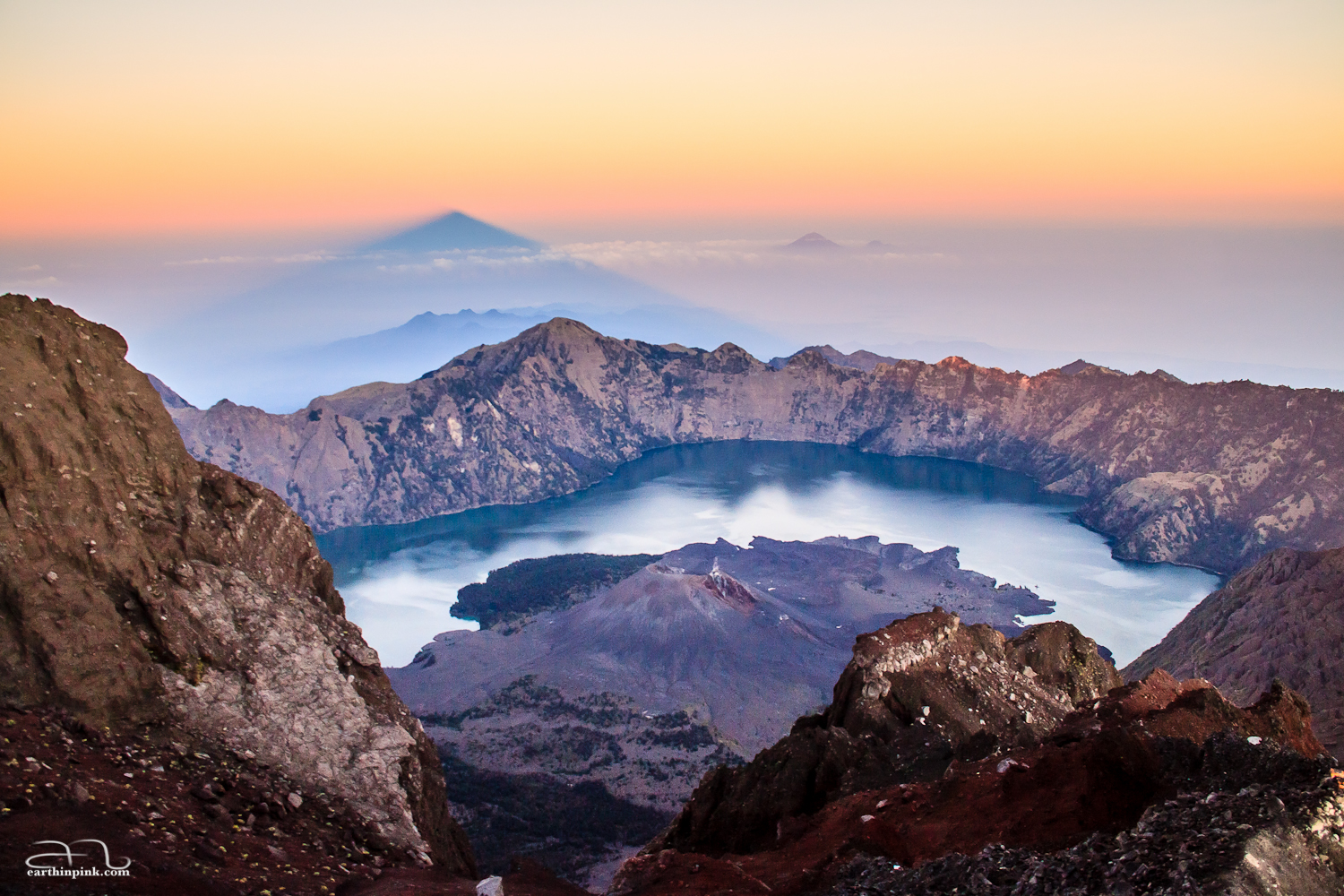 Sunrise from the peak of Gunung Rinjani, Lombok, Indonesia (3726m) showing both the crater lake and the shadow of the volcano.