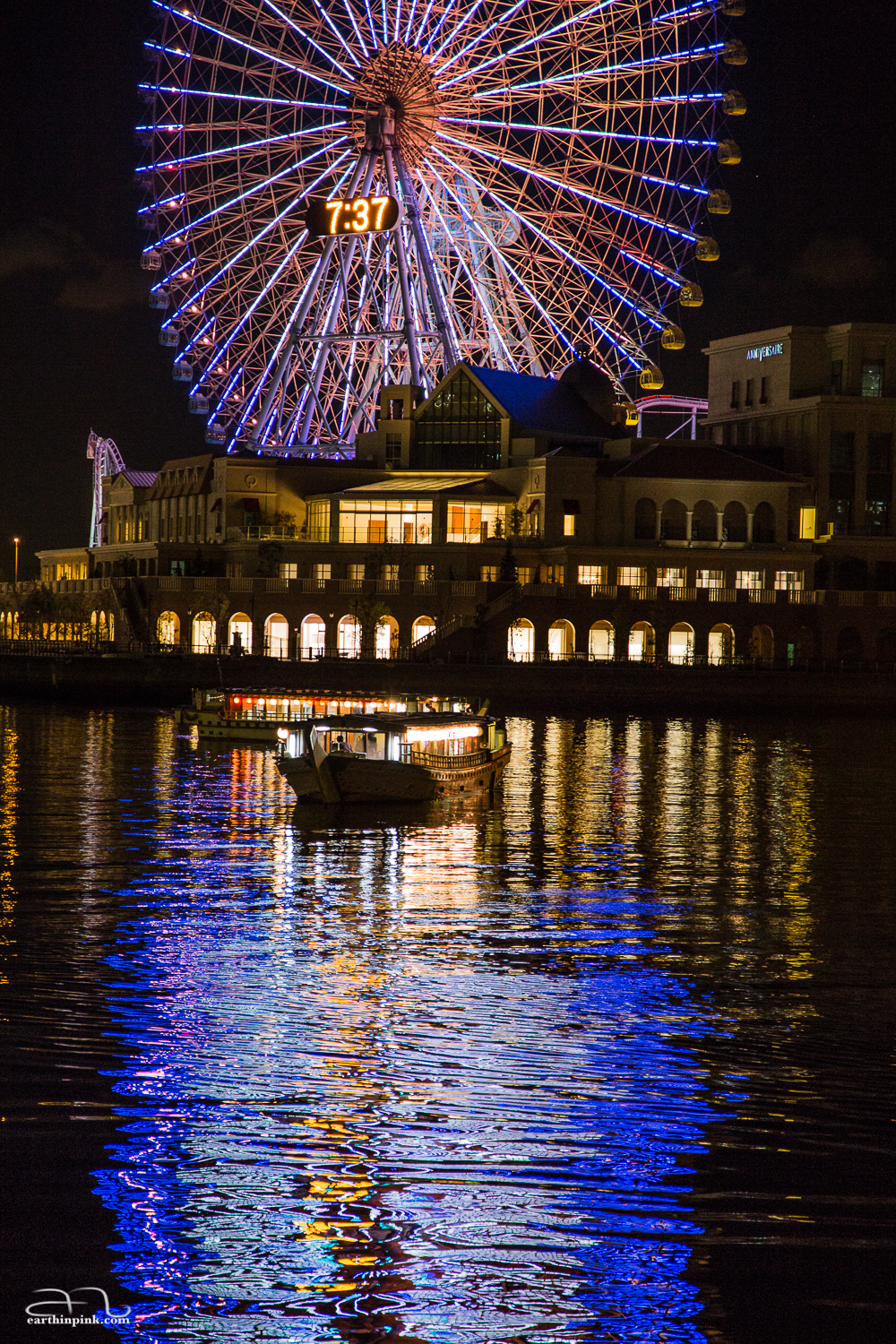 A boat riding on the reflection of the giant Ferris wheel at the Yokohama Cosmo World.