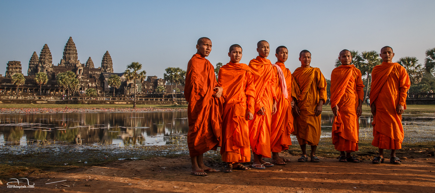 A group of Buddhist monks posing in front of the Angkor Wat temple at sunset on January 1st, 2014.