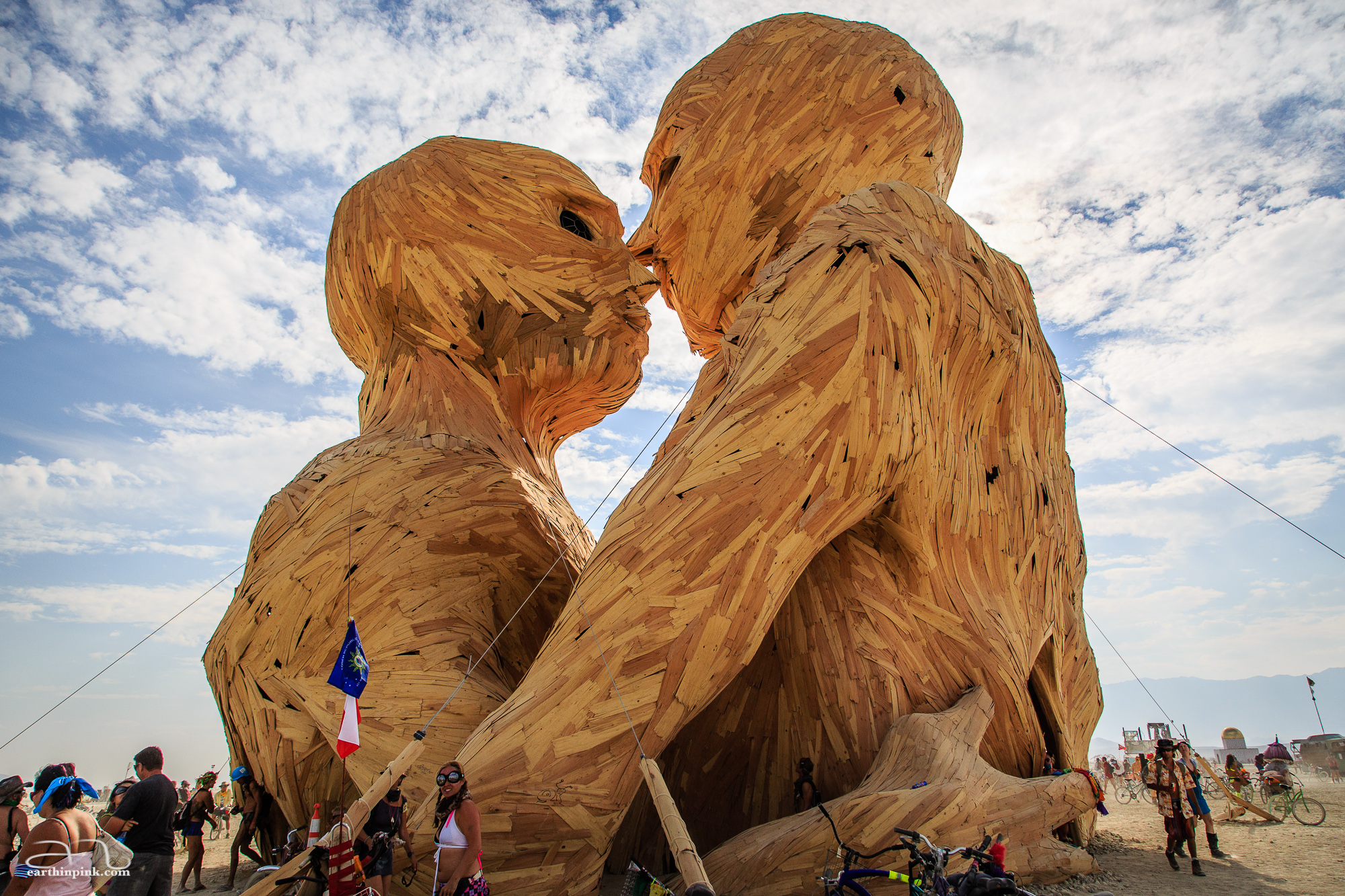 A 7 story tall wooden cathedral-like sculpture of two human figures in an embrace, built by The Pier Group.