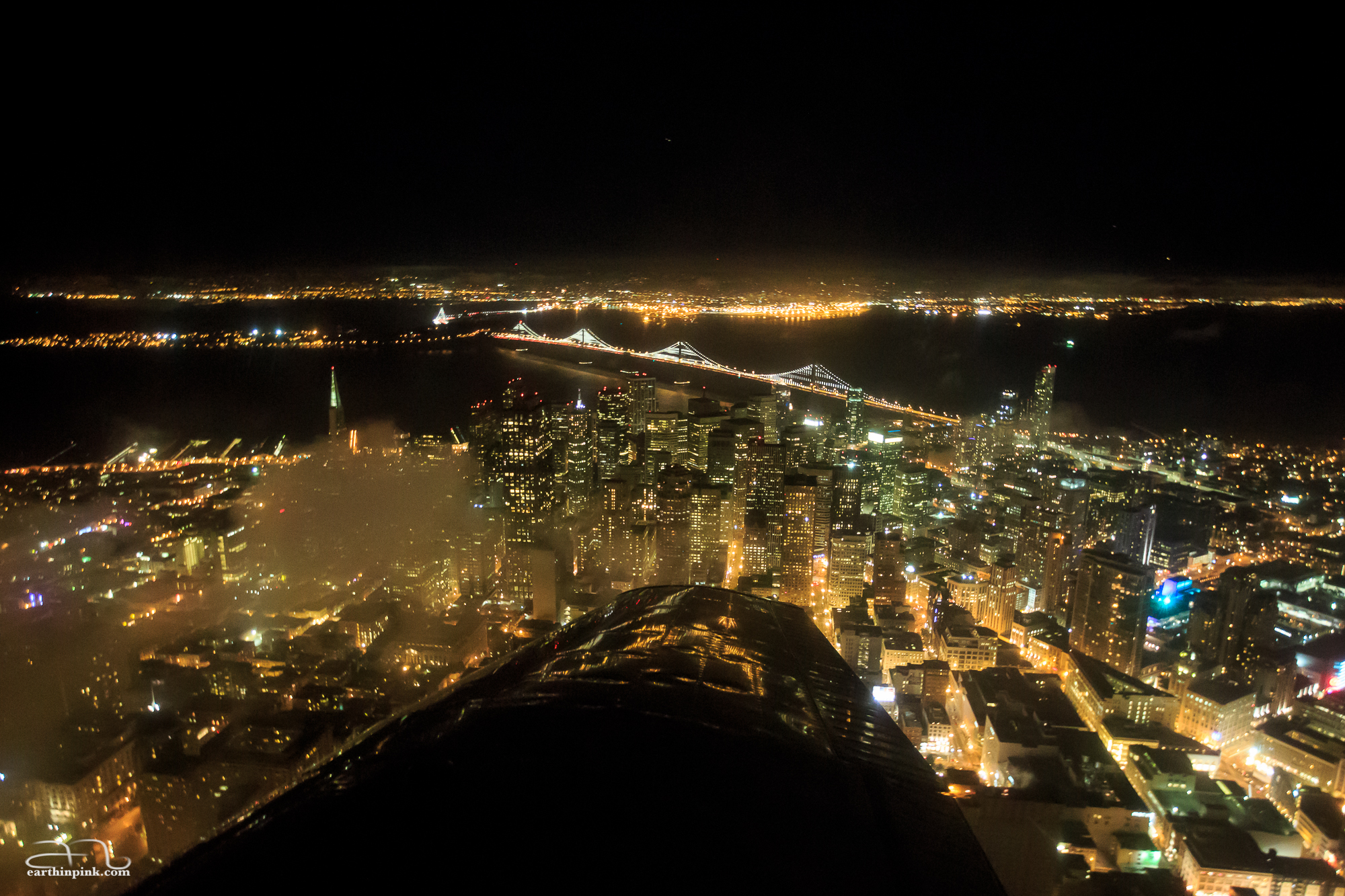 Night flight over San Francisco, with clouds rolling in.