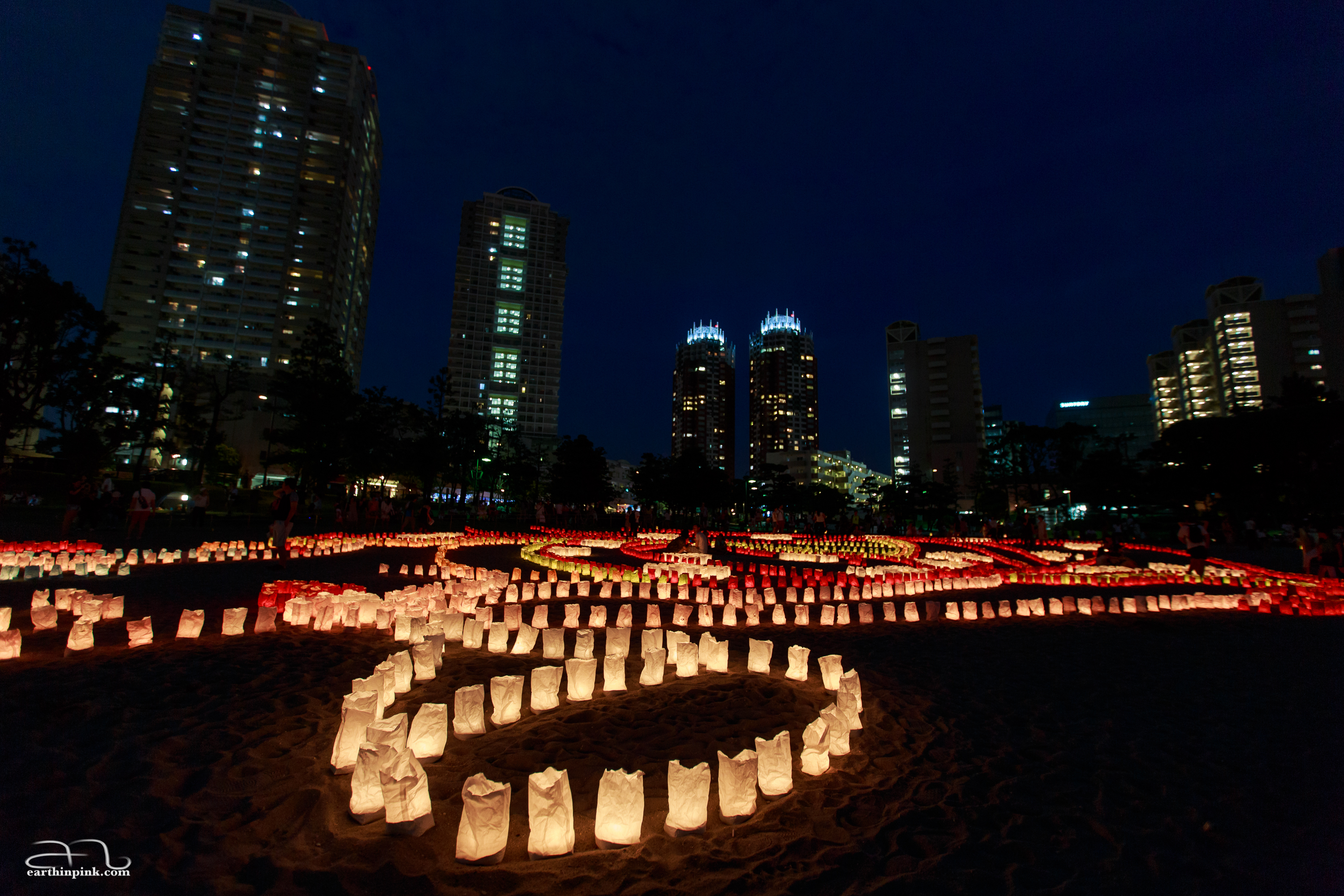Paper lanterns on the beach against a background of Tokyo skyscrapers.